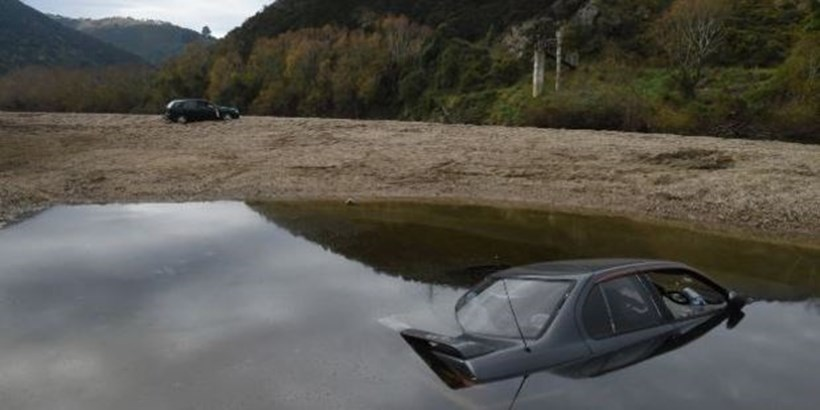 A Nissan Primera sits on the bed of the Taieri River, and a Nissan Sentra lies abandoned at Outram Glen. Photo / Otago Daily Times