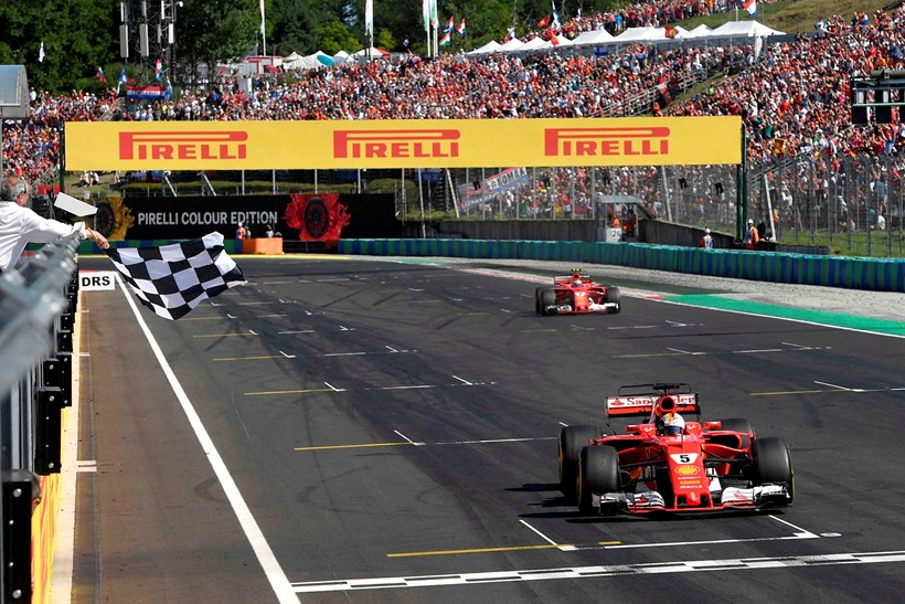 Sebastian Vettel takes the chequered flag in this weekend's Hungarian Grand Prix. Picture/AP
