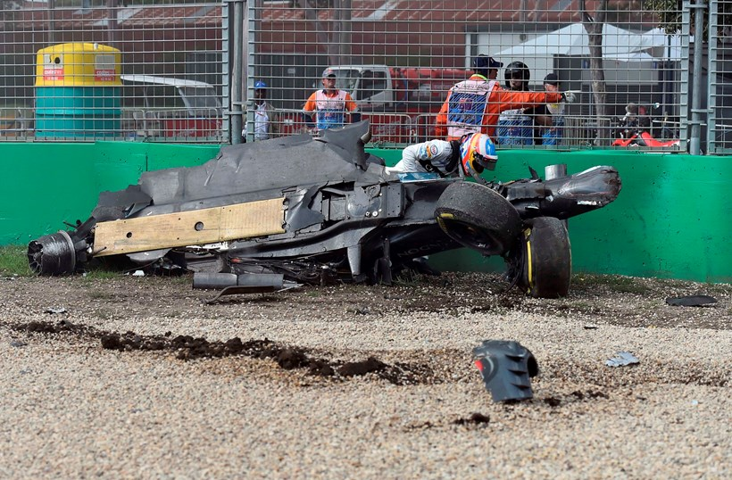 Alonso escaping from the wreckage after his spectacular crash during the Australian Grand Prix. Picture/AP.